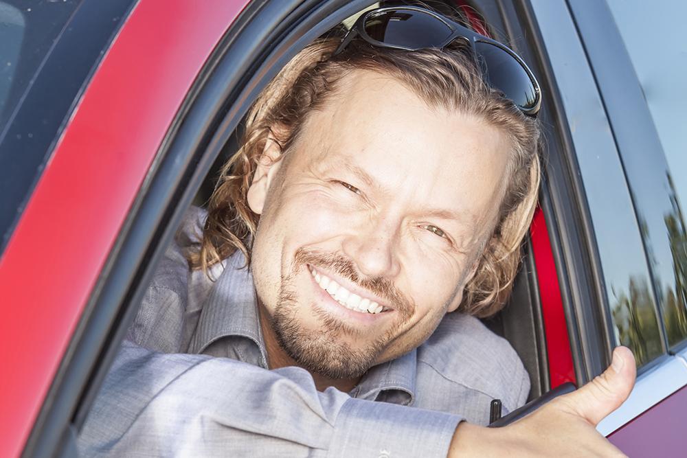 mies kurkistaa auton ikkunasta ja näyttää peukkua